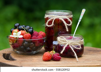 strawberry, blackcurrant and raspberry. Berry jam in a jar on wooden background.