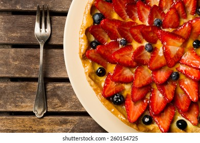 Strawberry and blueberry cake on wooden background. Composition with red fruits and a vintages fork