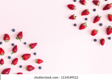 Strawberry and blueberry frame on pastel pink background. Flat lay, top view, copy space