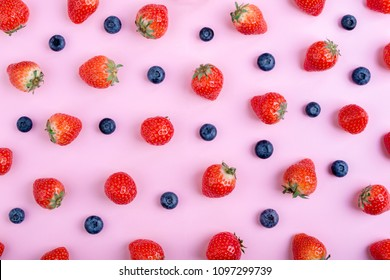 Strawberry and blueberry on pastel pink background, top view. Berries pattern, flat lay. Strawberry and blueberry isolated on pink background. Creative food concept