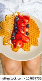 Strawberry, blueberry and raspberry on soft cheese over waffle on female lap at summer