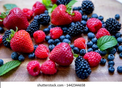 Strawberry, blueberry, raspberry variety on wooden and white background