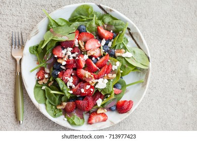Strawberry blueberry walnut spinach salad topped with a raspberry olive oil vinaigrette dressing and crumbled feta cheese full top view with fork