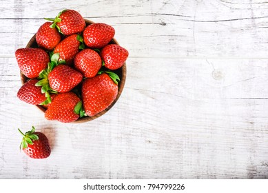 Strawberry in bow on white table. Strawberries top view. Beautiful strawberries