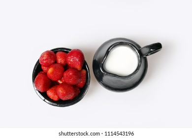 Strawberry in bowl and ceramic pitcher with milk on gray background - top view