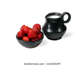 Strawberry in bowl and ceramic pitcher with milk isolated on white background