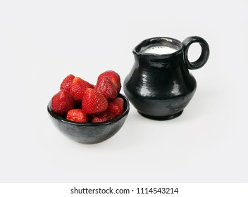 Strawberry in bowl and ceramic pitcher with milk on gray background