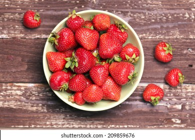 Strawberry in a bowl on wooden table close-up. Horizontal image