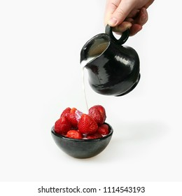 Strawberry in bowl under milk trickle pours from ceramic pitcher in hand on gray background