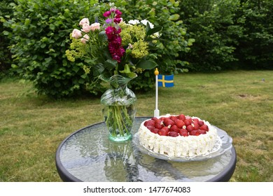 Strawberry cake with flowers and a swedish flag on a table in a green garden