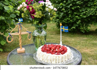 Strawberry cake on a midsummer decorated table in a green garden in Sweden