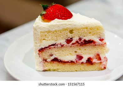 Strawberry cake on a white dish.