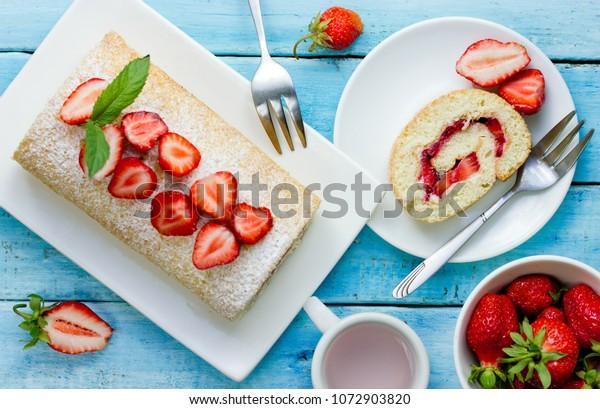 Gâteau aux fraises roulé sur fond bleu bois, vue de dessus