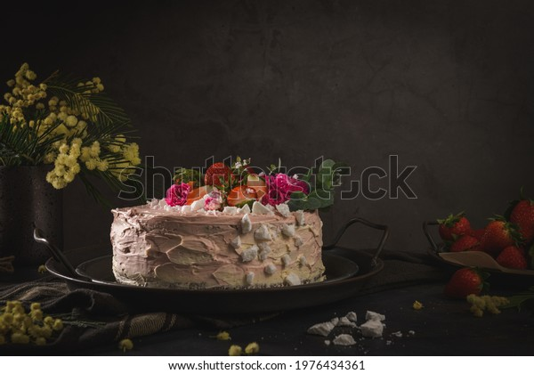 Strawberry cake, strawberry sponge cake with fresh strawberries and sour cream on a dark background.