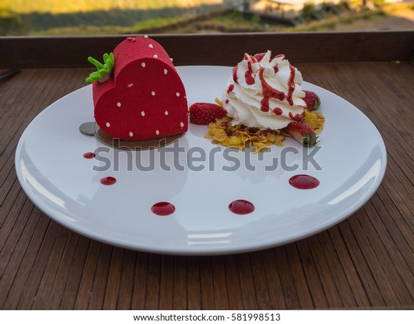 strawberry cake and whipping cream on wooden table