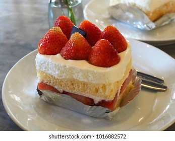 Strawberry cake in white plate on the table. If you eat with coffee is delicious.