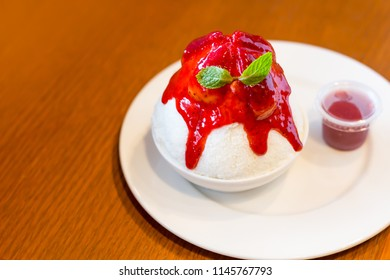 Strawberry Cheesecake Kakigori with Red sauce in white bowl on wooden table background and copy space.