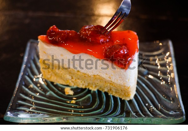 Strawberry cheesecake put the plate. Use a fork to cut the cake.