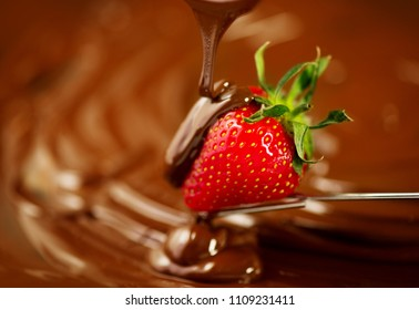 Strawberry in chocolate over swirl brown background. Melted Chocolate pouring on fresh ripe juicy strawberry close up. Dessert. Gourmet food. Fondue.