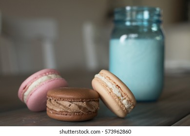 Strawberry, Chocolate, and Vanilla Macarons on Table in Front of Glass of Milk
