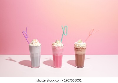 Strawberry, chocolate and vanilla milkshake with whipped cream on pink background. Place for text. Sweet drinks