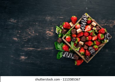 Strawberry with chocolate in a wooden box. On a wooden background. Top view. Copy space.