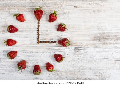 A strawberry clock with arrows from coffee beans showing a time of three or fifteen hours on a wooden vintage table in the kitchen