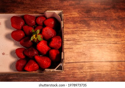 Strawberry crate with one strawberry shot on wooden table