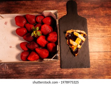 Strawberry crate with a slice of strawberry tart turned over on wooden table