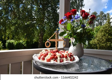Strawberry cream cake and summer decorations on a small table in a garden