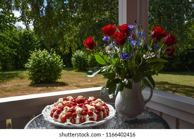 Strawberry cream cake and summer flowers on a small table in the garden