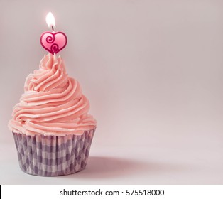 strawberry cream cupcake with heart candle on top and flame