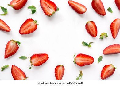 Strawberry creative pattern with copy space. Sliced ripe red berry with green leaves on white background.
