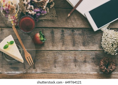 Strawberry crepe cake on wood table with copy space in top view flat lay. Food frame concept to present relaxing in cafe restaurant, enjoy eating during play smart phone.