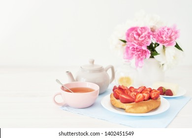 strawberry with croissant and tea on the table near a vase with peonies on a white background