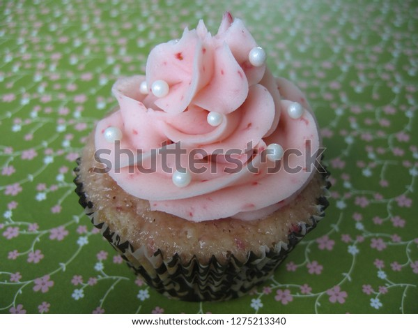 Strawberry cupcake with gorgeously pink strawberry frosting, garnished with white pearls