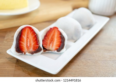Strawberry daifuku filling with red bean paste on white plate.