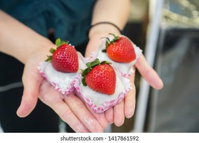 Strawberry Daifuku. Woman holding strawberry daifuku, A Japanese traditional dessert, topped with fresh strawberry.