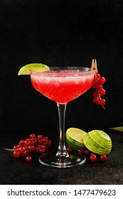 Strawberry daiquiri cocktail with lime, strawberry syrop, cherry and mint on black background. Summer drink, refreshment, Aperitif. Selective focus