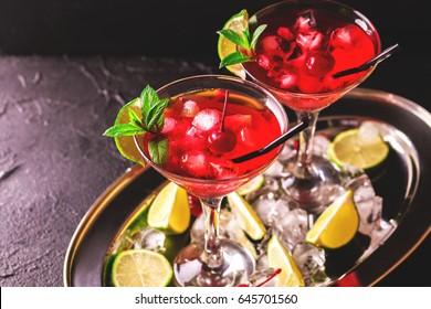 Strawberry daiquiri cocktail with lime, strawberry syrup, cherry and mint on black background. Summer drink, refreshment, Aperitif. Selective focus