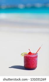 Strawberry daiquiri cocktail on a white sand beach