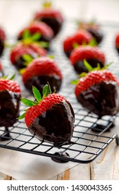 Strawberry dessert, Dark chocolate covered strawberries, fresh strawberries dipped in melted dark chocolate on a cooling tray