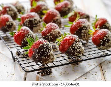 Strawberry dessert, Dark chocolate covered strawberries, fresh strawberries dipped in melted dark chocolate sprinkled with sesame seeds on a cooling tray