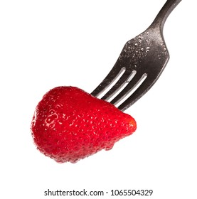 Strawberry dripping with moisture on a fork isolated on white