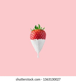 Strawberry with dripping white paint on pink background. Minimal food concept.