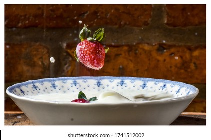 Strawberry falling on a plate of milk