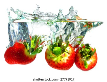 Strawberry falling in water, white background