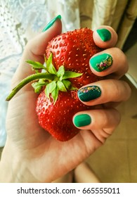 Strawberry in a female hand with a beautiful green manicure