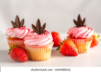 Strawberry flavoured pink cannabis infused cupcakes with chocolate cannabis leaf edible. CBD and THC muffins for patients who don't smoke medical marijuana. Valentines, birthday or mothers day party.