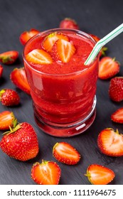Strawberry in fresh smoothie on black table. Healthy drinking concept. Focus on strawberry in glass with smoothie!